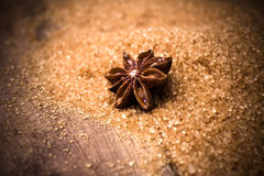 Anise star on brown cane sugar on wooden background, christmas s Stock Photo
