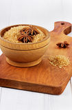 Anise star on brown cane sugar in a wooden cup. On a on a kitchen board Royalty Free Stock Image