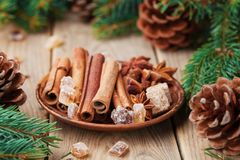 Anise star, cinnamon sticks and brown sugar in plate on wooden rustic table. Christmas spices. Royalty Free Stock Photo