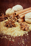 Anise star with cinnamon sticks and walnuts on brown cane sugar. On wooden surface Royalty Free Stock Images
