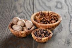 Anise stars cloves and nutmeg in olive bowl on oak Stock Photos