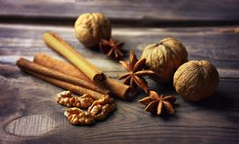 Anise stars, nuts, cinnamon, raisins for baking and cooking. Aromas of homemade food. Shallow depth of field. Star anise spice fruits and seeds on wood Stock Image