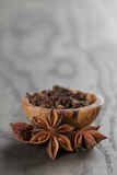 Anise stars in olive bowl on oak table, rustic Royalty Free Stock Photography