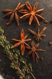 Anise stars and two sprigs of thyme. Five anise stars, two sprigs of thyme and black peper on old dark background. Selective focus Stock Images