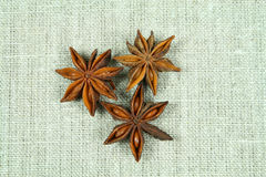 Aniseed on flax. Three anise stars on flax background Stock Photo