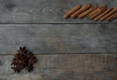 Anispeppar och kanelbruna pinnar på träbakgrund Royaltyfri Bild