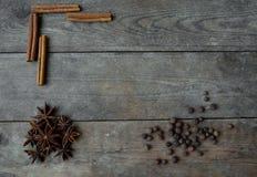Anispeppar och kanelbruna pinnar på träbakgrund Royaltyfri Fotografi