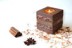 Anissterne, Zimtstangen und Aromakerze auf weißem Hintergrund Stockfoto