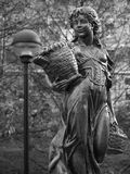 Anita Black & White. Statue of a young woman taking baskets Royalty Free Stock Photo