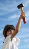 Anita and the hammer. European girl posing raising the hammer in the sky Royalty Free Stock Photos