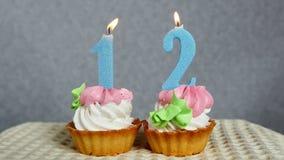 12 aniversário feliz, velas azuis de queimadura do número em queques filme