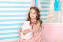 Aniversário! Menina bonita que senta-se com presentes Barra do aniversário dos doces Retrato de um close up da cara do bebê Pouco fotografia de stock royalty free