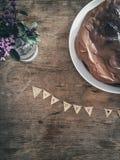 Aniversário perfeito com flores violetas, um bolo e desejos bonitos Imagem de Stock