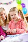 Aniversário: Menina do aniversário que faz o ofício no partido Imagens de Stock Royalty Free