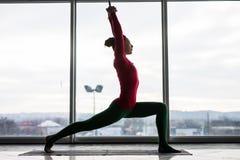 Anjaneyasana Όμορφο ημισεληνοειδές lunge πρακτικής γυναικών γιόγκας θέτει σε ένα μεγάλο παράθυρο Στοκ Εικόνες