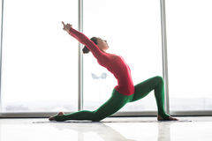 Anjaneyasana. Beautiful yoga woman practice crescent lunge poses in a big window. Hall background. Yoga concept stock photography