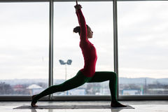 Anjaneyasana. Beautiful yoga woman practice crescent lunge poses in a big window. Hall background. Yoga concept stock images