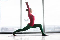 Anjaneyasana. Beautiful yoga woman practice crescent lunge poses. In a big window hall background. Yoga concept royalty free stock images