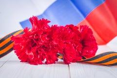 Anjer en lint van St George, als symbool van overwinning tegen de achtergrond van de Russische vlag 9 mei, de dag van overwinning Stock Foto