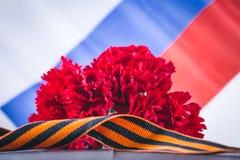 Anjer en lint van St George, als symbool van overwinning tegen de achtergrond van de Russische vlag 9 mei, de dag van overwinning Royalty-vrije Stock Foto's