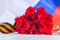 Anjer en lint van St George, als symbool van overwinning tegen de achtergrond van de Russische vlag 9 mei, de dag van overwinning Royalty-vrije Stock Foto