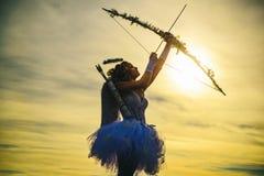Anjo adolescente Arqueiro adolescente da menina do anjo no por do sol Silhueta de um cupido Opini?o lateral o arqueiro adolescent fotografia de stock