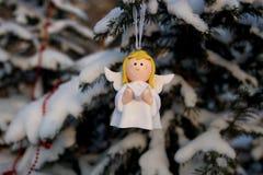 Anjo com um livro em suas mãos em um ramo coberto de neve no p fotos de stock royalty free