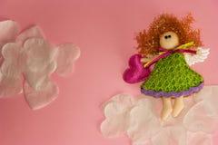 Anjo do brinquedo nas nuvens dos corações brancos imagens de stock