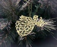 Anjo do ouro que pendura na véspera, fundo do Natal Imagens de Stock Royalty Free