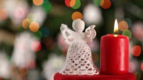 Anjo feito crochê do xmas e vela ardente no fundo obscuro da árvore de Natal filme