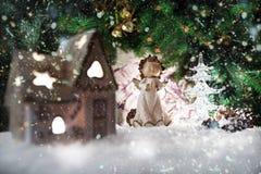 Anjo na casa e na árvore de Natal com luzes e reflexões no fundo de temas do Natal Foto de Stock Royalty Free