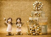 Anjos pequenos com presentes Curva da fita no fundo dourado Foto de Stock Royalty Free