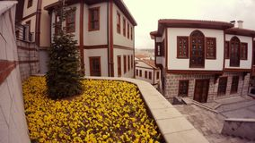 Lowerbed with yellow flowers and small white houses old Ankara. Ankara capital of Turkey cityscape early spring stock video footage
