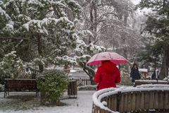Ankara/die Türkei 6. Dezember 2019: Mädchen im roten Mantel unter rotem Regenschirm im Winter lizenzfreies stockbild