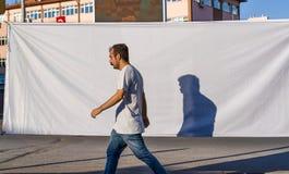 Ankara/Turchia 23 giugno 2019: Un pedone che cammina con la sua ombra sui precedenti bianchi fotografia stock libera da diritti