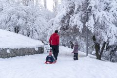Ankara/Turkey - December 26 2018: Back view of father sledding his little baby and another daughter walk with them in Segmenler royalty free stock photography