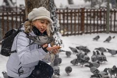 Ankara/Turkey-December 06 2018: Woman feeding pigeon on his hand with simit which is Turkish bagel stock photography