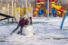 Ankara/Turkey-January 01 2018: Two girls rolls a big and heavy snowball to build a snow man in a play ground in winter stock photography