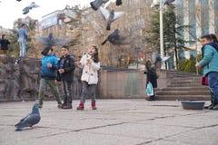 Ankara/Turkey-March 3 2018: Children feeding pigeons and enjoying the day in Kizilay, City center of Ankara stock photo