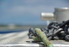 Ankerketting en kabel op de voorzijde van boot met het verankeren van punt op de achtergrond Stock Fotografie