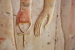 Ankh, ancient symbol also known as key of life, Egypt. Ankh, an ancient Egyptian symbol of eternal life, in hand of a god, on the wall of the temple near Luxor Stock Image