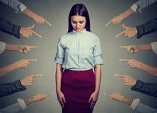 Anklage der schuldigen Person Traurige Frau, die hinunter die Finger zeigen auf sie schaut Stockfotografie