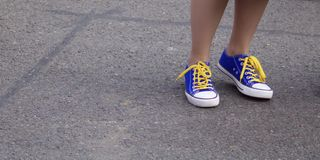 Anklar av flickan som bär blåa sportskor med guling, snör åt mot grå trottoarbakgrund - bild royaltyfri fotografi