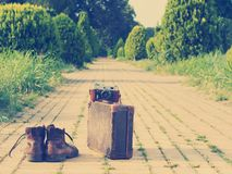 Ankle boots, cardboard suitcase, film camera, brick road. Post-processed. Royalty Free Stock Photo