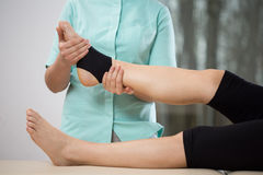 Ankle manipulation. Young physiotherapist doing ankle manipulation to elderly woman Royalty Free Stock Images