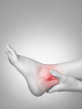 Ankle pain. A young woman massaging her painful ankle Royalty Free Stock Photography