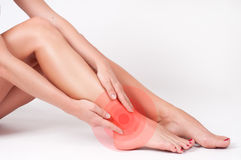 Ankle pain. Female legs. Woman massaging her ankle. Ankle pain. Woman touching her injured foot. Female legs on white background Stock Photos