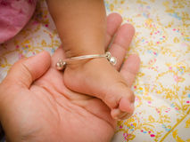 Anklet of newborns in mom's hand Stock Photo