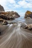 Ankommender Wasserstrom am karminroten Strand Stockbild