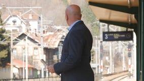 Ankomst för affärsmanIn Railway Station väntande drev arkivbild